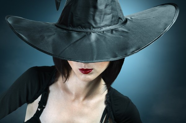 Young woman in a witch costume her face covered with a hat